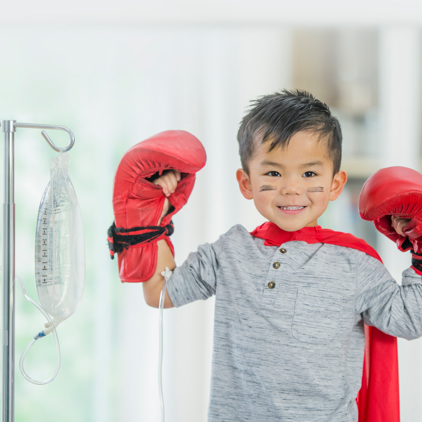 Little boy getting iv treatment wearing cape and boxing gloves