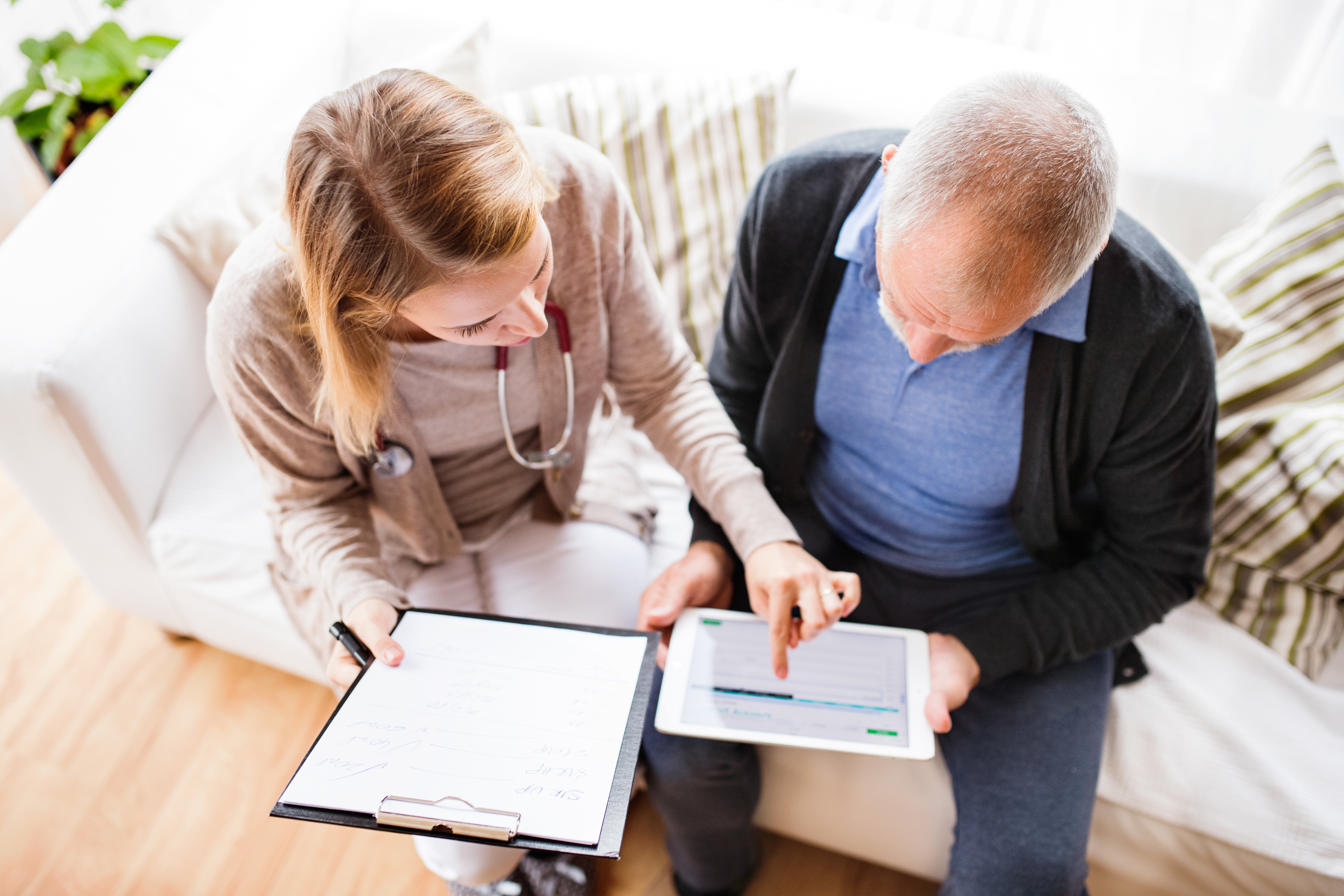 health visitor and a senior man with tablet during home visit