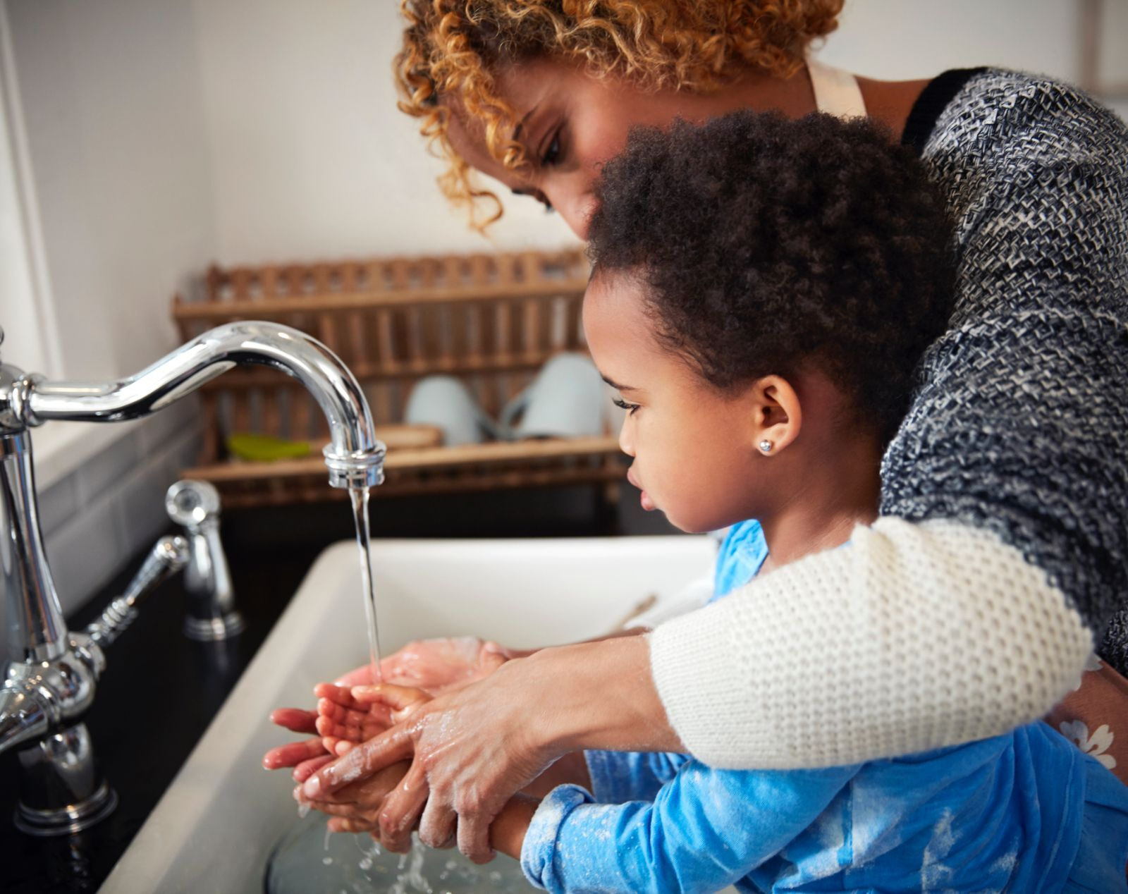 mother helping small child in blue shirt wash his hands at kitchen sink