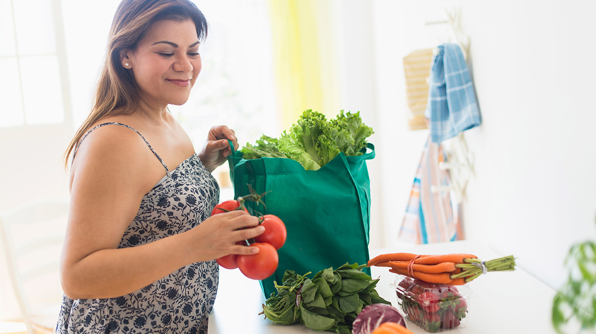 Woman taking out produce from grocery bag