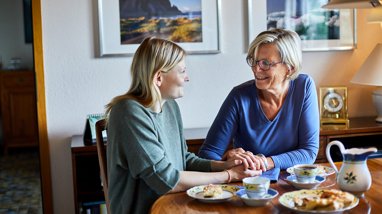 mother and adult daughter sitting at dining table each pastries and drinking tea while holding hands