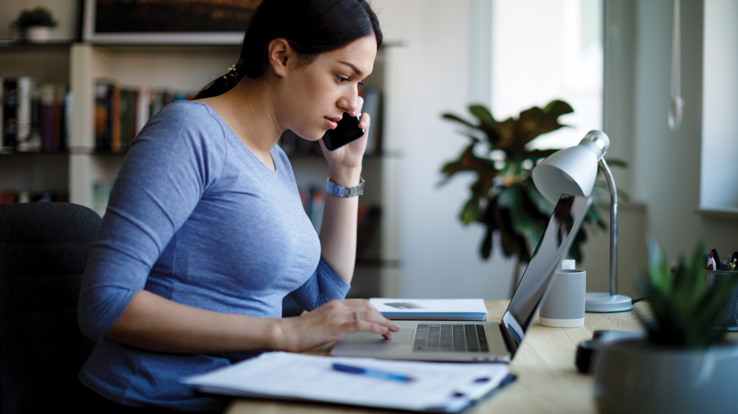 woman on her phone in front of laptop at home desk