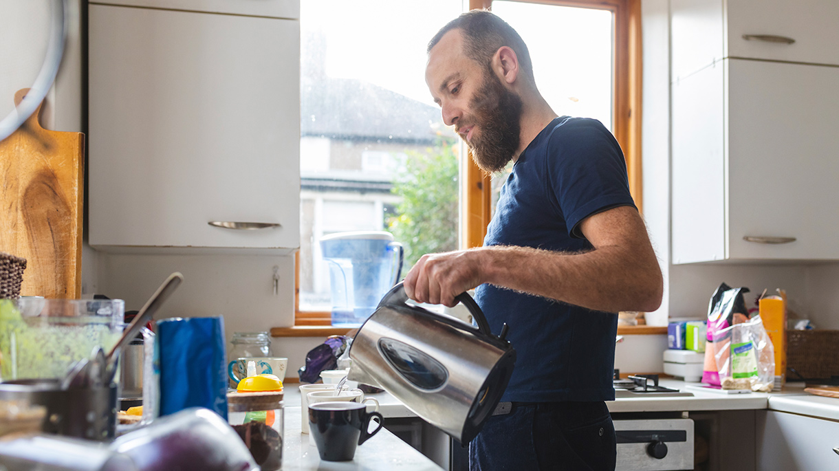 Man pouring hot water from kettle into mugs