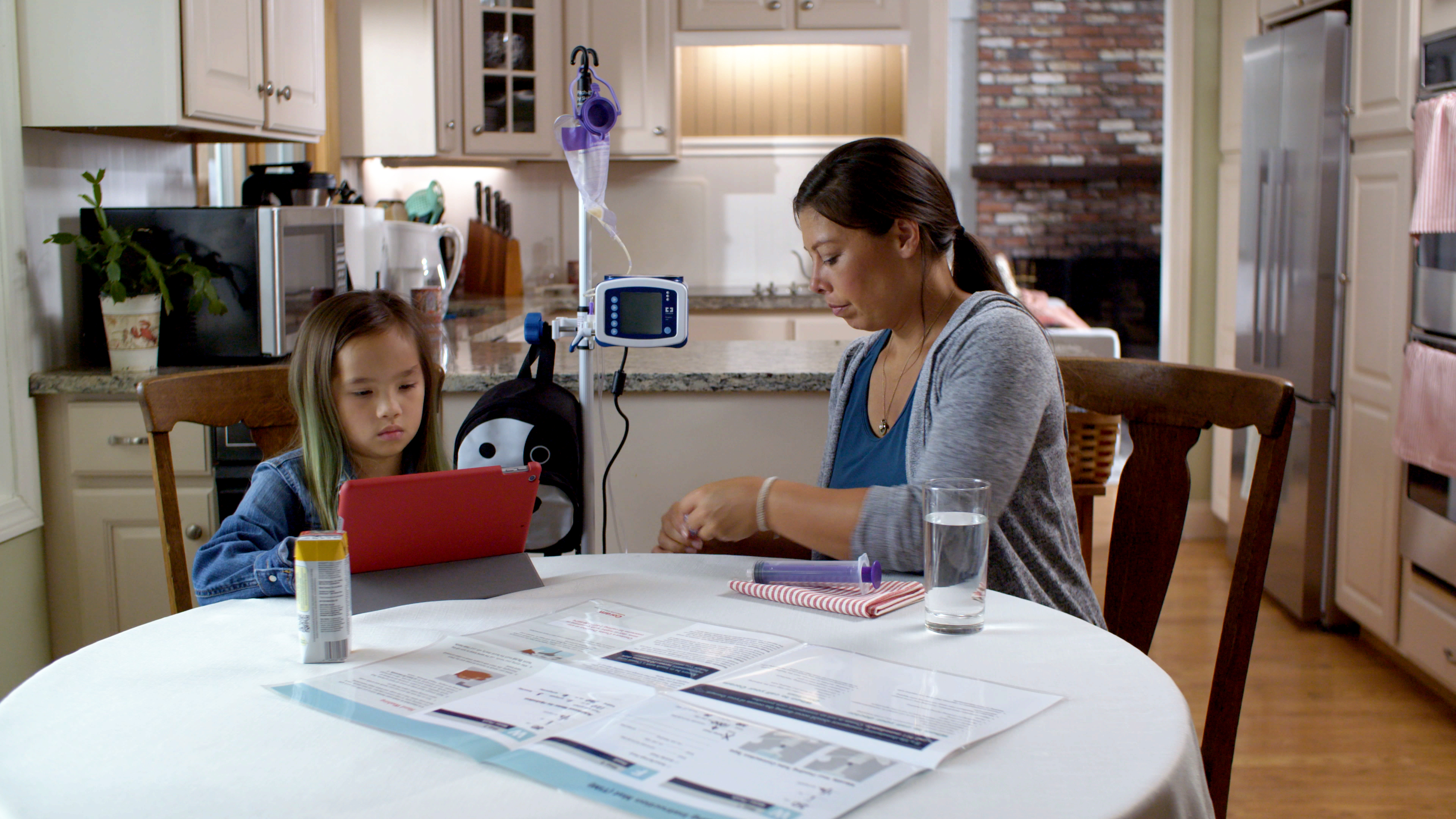 mother and daughter at kitchen table while daughter watches iPad while getting therapy