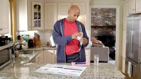 A man prepares formula for tube feeding in his kitchen.